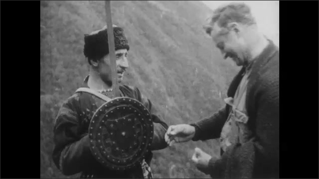 1940s: CAUCASUS, EUROPE: man holds chain mail in hand. Man looks at cross on shield. Men with swords and shields fight in mountains