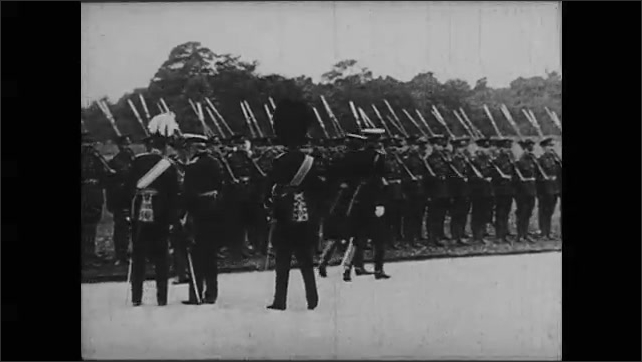 1910s: Man in uniform is draped in coat then escorted by guards in uniforms onto horse drawn carriage. Generals march in front of soldiers standing at attention. Men in uniforms approach house.