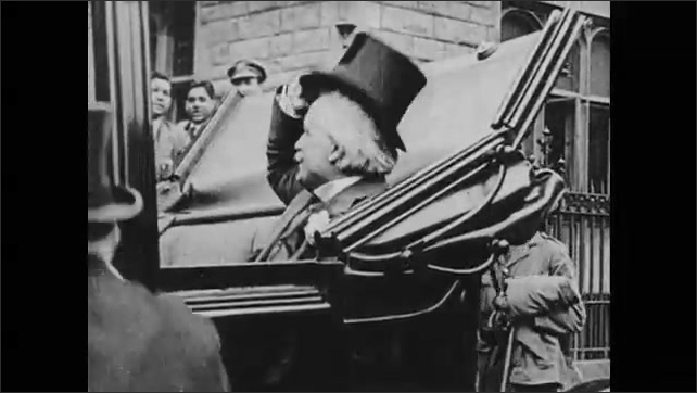 1910s: Men in suits walk down steps surrounded by cheering crowd. Man in top hat gets in open-air car and doffs hat.