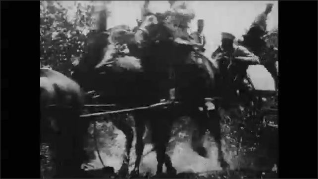 1910s: Soldiers marching. Soldiers on horses come over hill. Men in uniforms on horses.