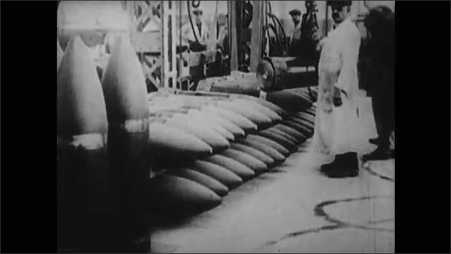 1910s: Barrell for cannon is hoisted on crane in factory. Men turn cannon on mount. Wood in lathe. Bombs laid in rows. Soldiers marching.