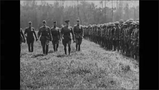 1910s: Soldiers climb out of trenches as ground explodes around them. Soldiers storm out of trenches. Commanders walk in front of soldiers standing at attention. Soldiers march.