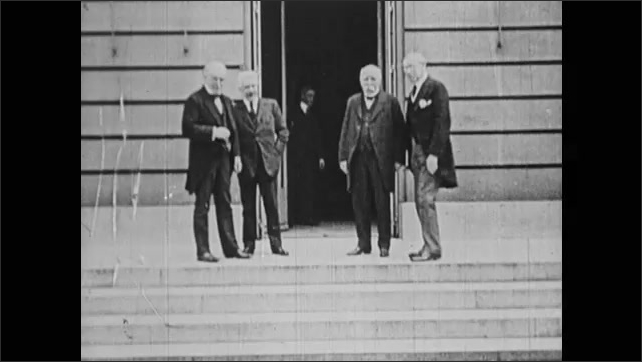 1910s: Four men walk out of building and stand talking. Signatures on pages.