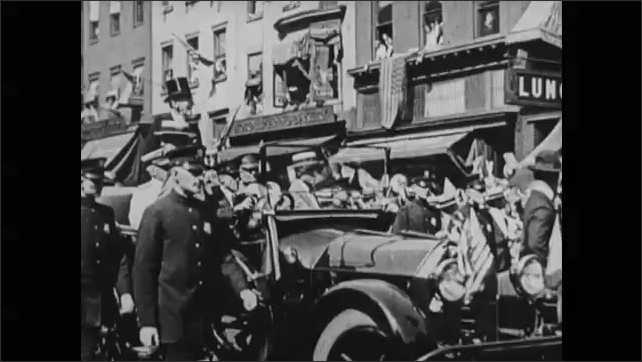 1910s: Man in top hat on boat. People in vehicles in parade down street.