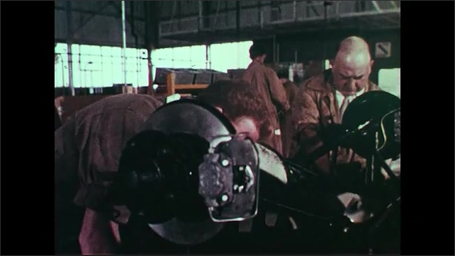 United States: 1960s: wheels and engine of Rover 2000 being built. Mechanics work on car. Car engine lowered into new vehicle in factory.