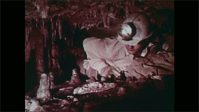 1960s: UNITED STATES: caver crawls through small space. Caver pushes bag ahead of him. Speciation inside cave environment. Insect on wall of cave. Stalactites above caver