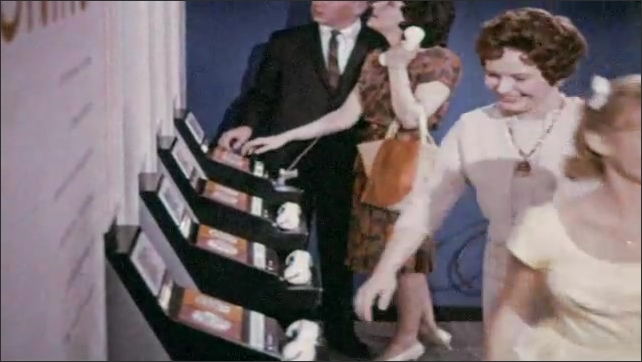 1960s: Hand turns dial on display. Close up, hand pushes buttons. Boy and girl hang up phones, exit. Crowd gathers around woman speaking in front of display.