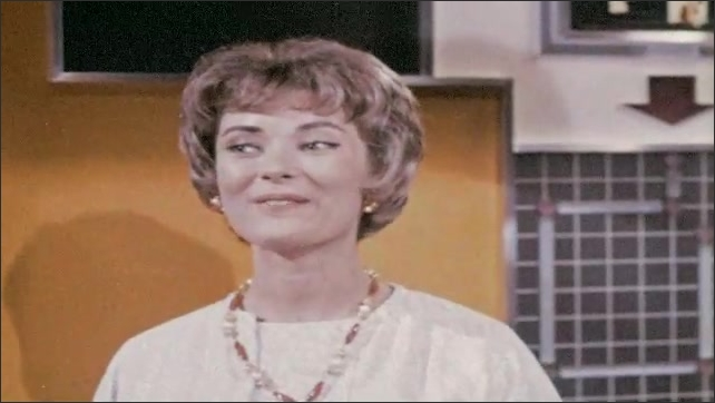 1960s: Image on screen, woman hands phone to other woman. Close up of woman talking. Image on screen, woman on phone, zoom out to woman at desk.