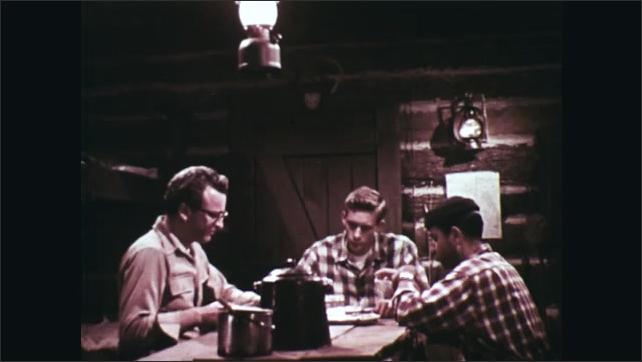 1960s: Man eating at table. Men at table, man enters door in background.