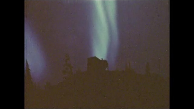 1980s: Hillside silhouetted against aurora borealis or the Northern Lights.??