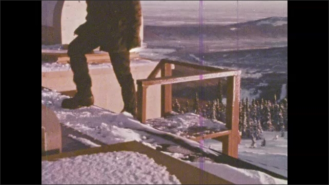 1980s:??Scientist makes notes looking at readout. Observatory in the snow. Student climbs stairs to roof of observatory.??