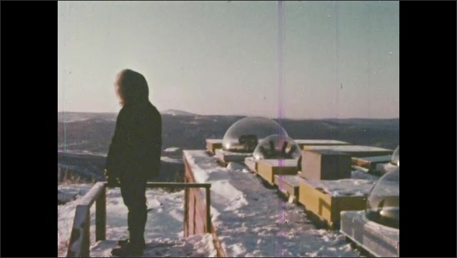 1980s:Man puts head into bubble on roof of observatory to observe conditions. Needles move on a panel of instruments.