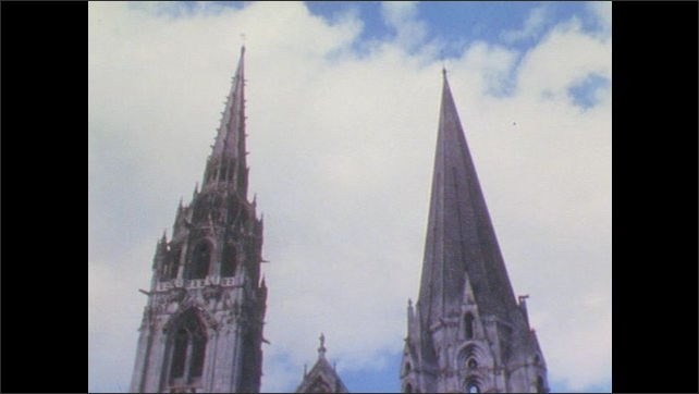 France 1960s: Silhouette of cathedral arch and slats between columns to sky. Two gothic spires against sky, airplane passes behind.