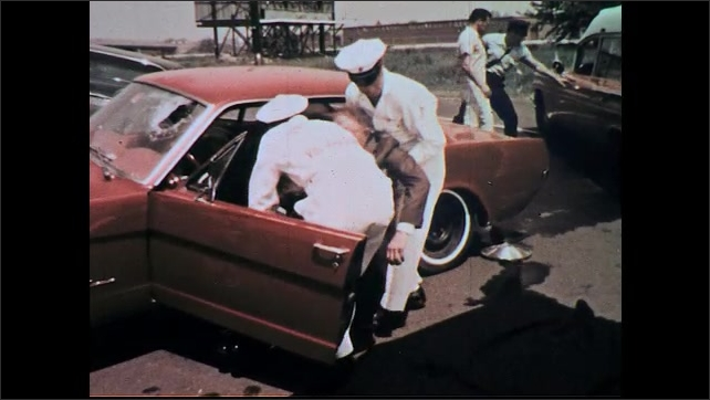 UNITED STATES 1960s: High angle view, medics help man from car / Medics pull man from car, lay him on ground, zoom in on man.