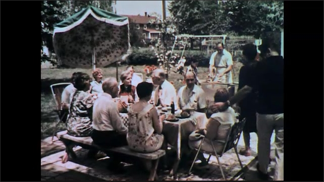UNITED STATES 1960s: Kids on swings, boy jumps off, runs toward camera, zoom out to people at picnic.