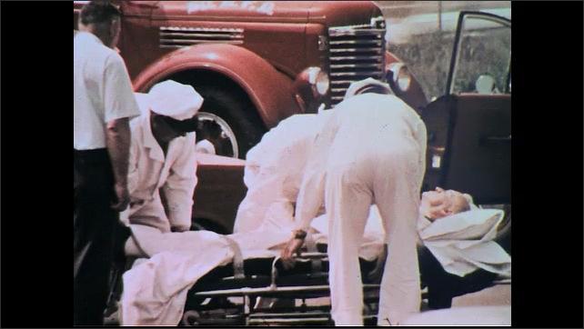 UNITED STATES 1960s: Medics strap man onto stretcher, put him in ambulance.