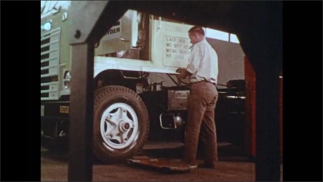 1970s: UNITED STATES: Man works under truck on rolling board. Man puts cloth in pocket. Man climbs into cab of truck. Keys in ignition. Man turns key