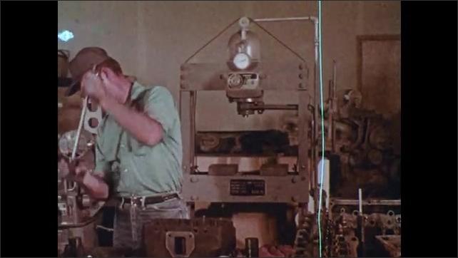 1970s: UNITED STATES: man loosens metal object in workshop. Man hits metal.