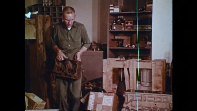 1970s: UNITED STATES: man enters workshop. Man lifts heavy object from ground. Oil on ground. Puddle on floor. Cardboard box on ground