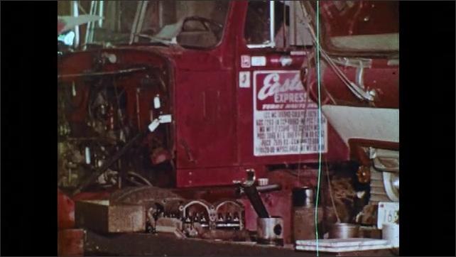 1970s: UNITED STATES: engine on ground. Truck in garage. Wear Your Goggles sign. Fire extinguisher in garage