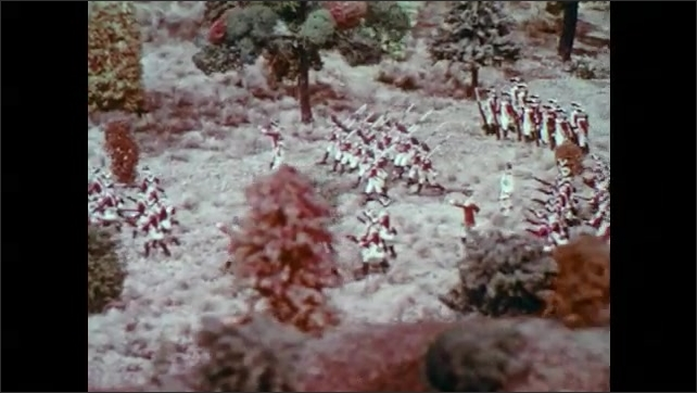 1970s: Military figurines on a model landscape. Wargaming figures in marching formation. British soldier models on fake terrain.