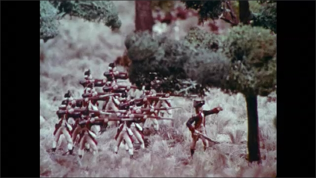 1970s: Military figurines on a landscape. Wargaming figures in fighting formation. British soldier models and miniature cannons on fake terrain. Revolutionary soldier models face British soldiers.