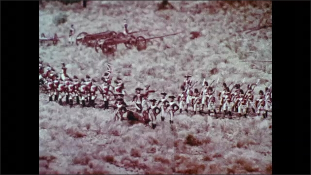 1970s: Military figurines on a model landscape. Wargaming figures in marching formation. British soldier models on fake terrain. Large branch overlooks grassy field.