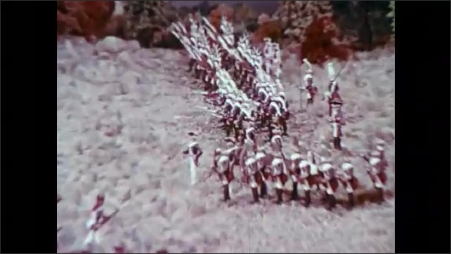 1970s: Military toy figures on a landscape. Wargaming figures in fighting formation. British soldier models and miniature cannons on fake terrain. Revolutionary soldier models face British soldiers.