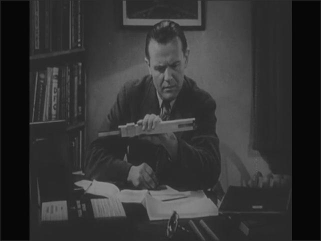 1950s: Man sits at desk working. Man grabs slide ruler instrument and writes down information. Men work on conveyor belt. Man looks over seated man