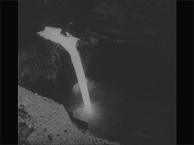 1950s: Fire burns in industrial furnace. Lava flows down dirt hills and into water. Machine dumps rocks into container.