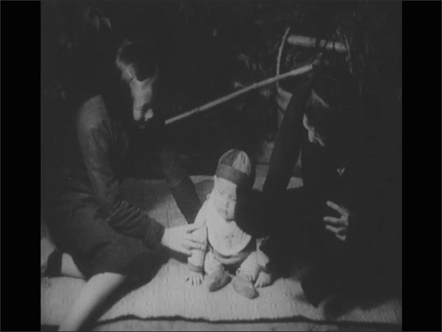 1940s: young boy washes hands, two adults play with a baby