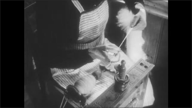 1950s: Close up, hand slices bread. Low angle view, woman at spinning wheel. Hands spin thread. Woman at spinning wheel.