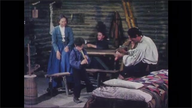 1950s: Family inside log cabin. Boy plays instrument, dances. Man claps. Girl plays with doll. Women sing and smile.