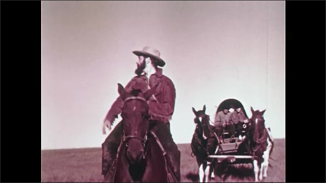1950s: Man riding horse. Long shot, train of covered wagons on trail. Man on horseback in front of wagon, stops, gets off horse.