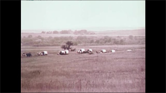 1950s: Long shot of wagon train traveling across prairie. Close up of wagon wheels in grass.