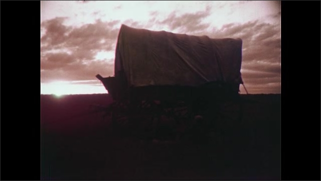 1950s: Wagon wheels in grass. Rear view, woman and boy riding in wagon. Woman and girl in wagon. Long shot of wagons. Wagon, sunrise in background. Man wakes up next to wagon. Boy gathers sticks.