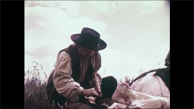 1950s: Man shoots gun.  Buffaloes fall.  Herd runs.  Man skins buffalo.  Woman is surprised by Native Americans.  Man smiles.