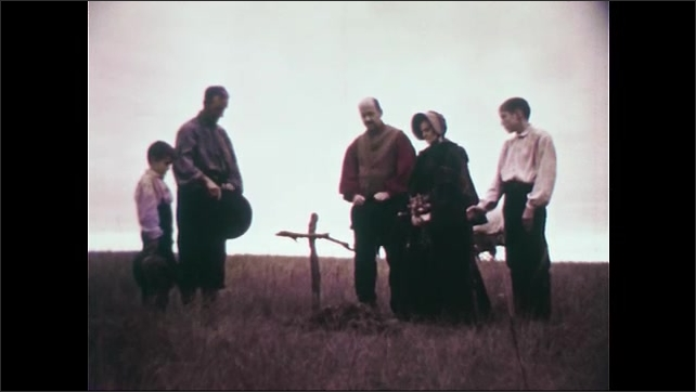 1950s: Gravestone.  Family stands at grave.  Man prays.  Men remove hats.