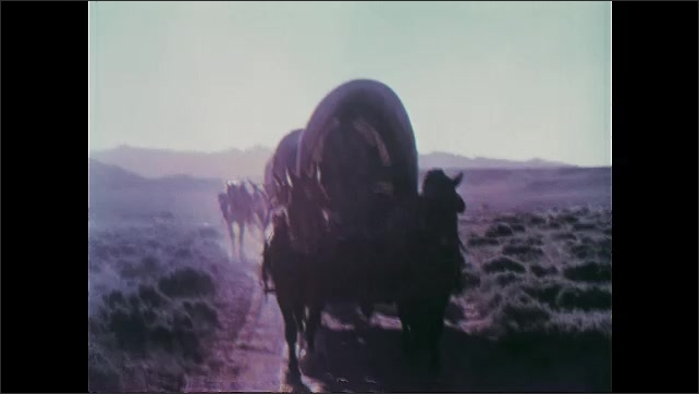 1950s: Sagebrush.  Wagon train moves along.  Man on horse.  Native Americans ride up on horses.