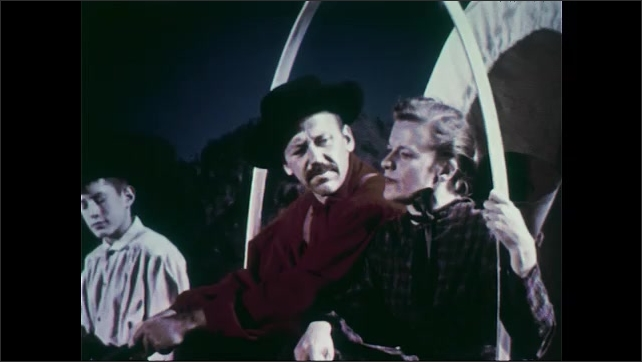 1950s: Mountains.  Wagon train travels along.  Man and woman talk.  Boy thinks.