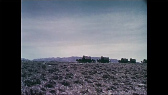 1950s: Wagon train travels along.  Mountains.