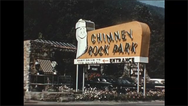 1950s: Sun rises into sky. Flag moves gently on flagpole. Letters on chimney rock state park sign move back and forth. Flowers. Sign in front of chimney rock. Man looks through viewfinder.