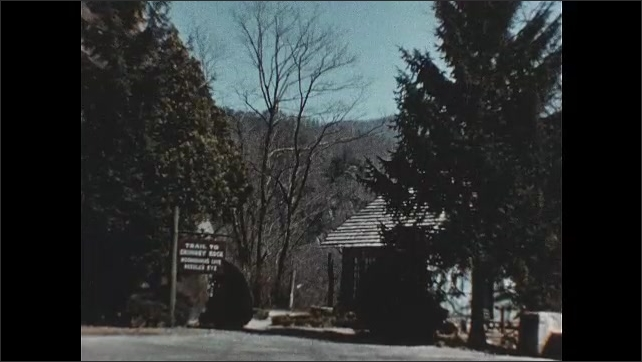 1950s: Lake surrounded by mountains. Cars drive on road below mountain. Trailhead for Chimney Rock. People walk into building marked elevator.