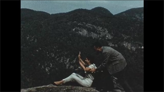 1950s: Man and woman walk along mountain trail. Man feels tree. Woman sits on rock, man sneaks up behind and scares her.