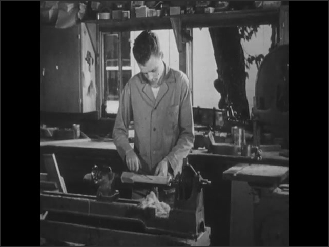 1950s: teenage boy in jumpsuit measures wood on lathe as girl in striped dress enters workshop, turns off radio and talks near woodworking equipment.