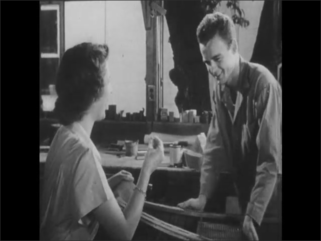 1950s: teenage boy in jumpsuit removes splinter from finger of girl next to canoe in workshop. girls ride horses farm pasture with white wood fences and a silo near woods and hill.