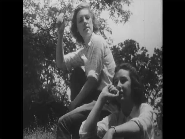 1950s:  two teenage girls sit on tree stump and talk in field near woods.