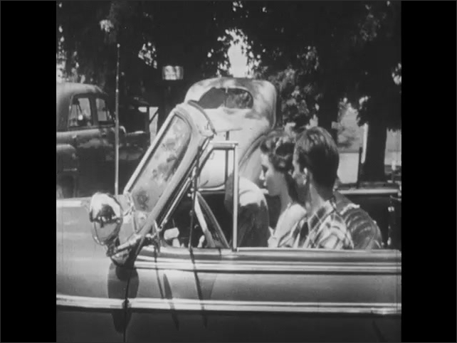 1950s: teenage boy in plaid shirt leans against convertible, talks to girl in swimsuit behind steering wheel, opens car door, sits on driver's seat and drives away.