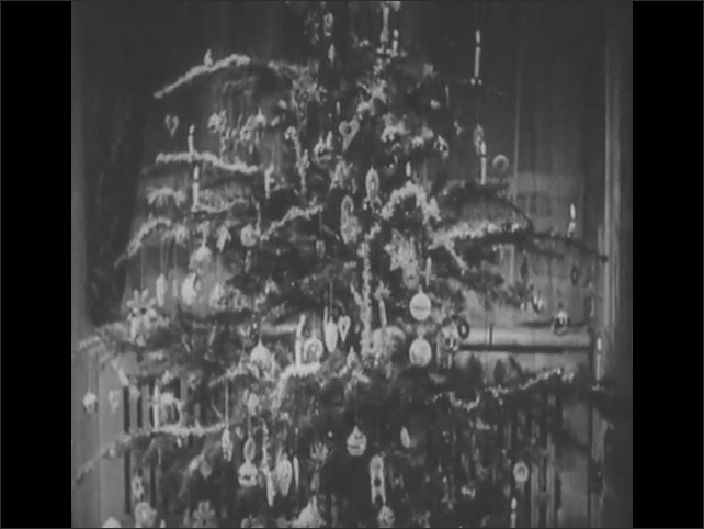 1940s: Young girl plays with toys under Christmas tree: a doll, a teddy bear, and a giraffe. Christmas tree from bottom to top decorated. Candle on branch Christmas tree rapidly melts down.