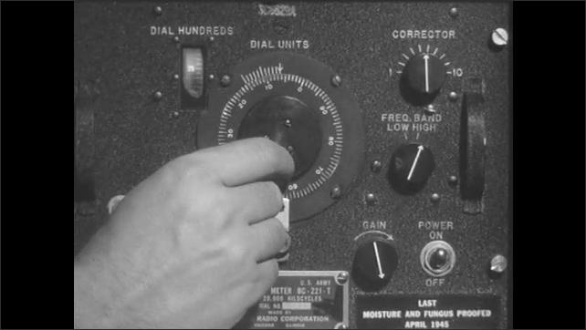 1950s: Man turns various dials on radios.